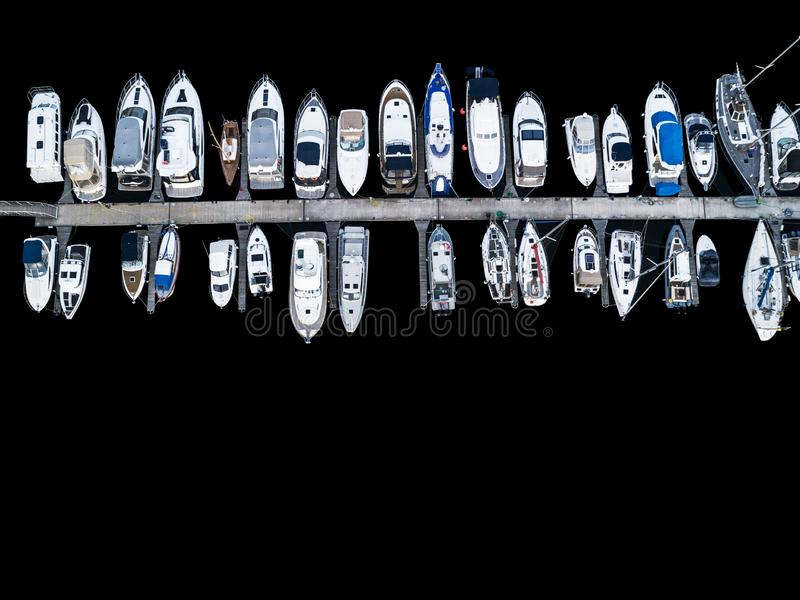 Aerial View by Drone of Yacht Club and Marina. Top view of yacht club. White boats in sea water. Marina dock yachts and small moto. R boats. Yacht and sailboat stock photo