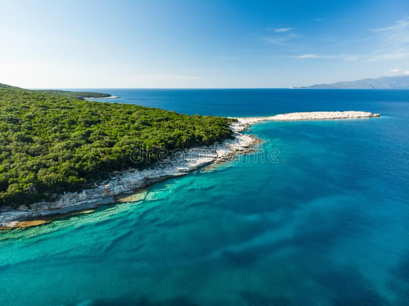 Aerial view of Emplisi Beach, picturesque stony beach in a secluded bay, with clear waters popular for snorkelling. Small pebble. Beach near Fiscardo town of royalty free stock photos