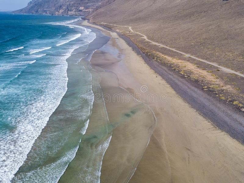 Aerial view of Famara beach, Lanzarote, Canary Islands, Spain. Risco di Famara, relief, mountains overlooking the Atlantic Ocean. Unpaved road that runs along royalty free stock photo