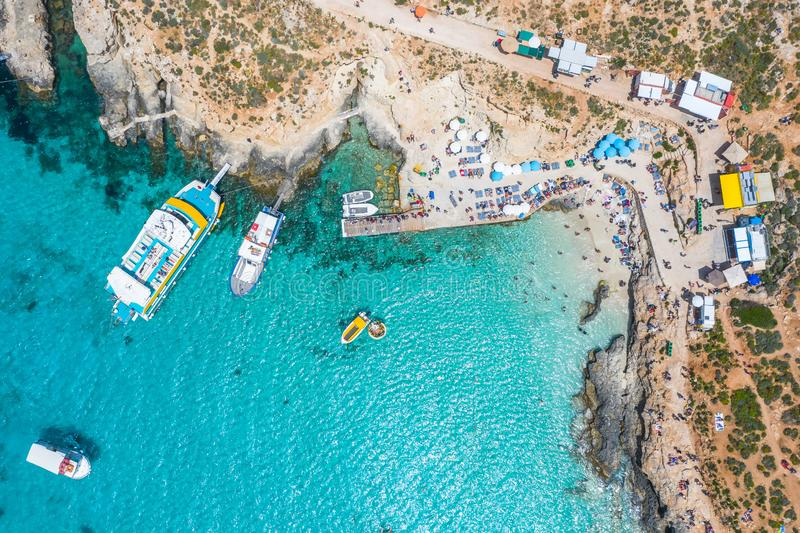 Aerial view famous Blue Lagoon in the Mediterranean Sea. Comino Island, Malta. Beach and vacationers, a bay pier with ships and royalty free stock photography