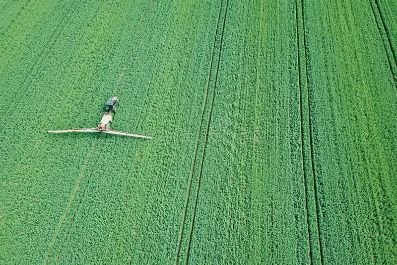 Aerial view Farm machinery spraying chemicals on the large green. Field, agricultural spring background. Agriculture Aerial stock image