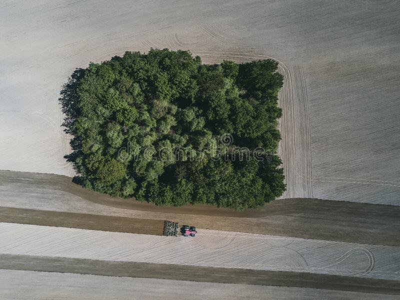 Aerial view of a farm tractor in a field during plowing of land for growing food. stock image