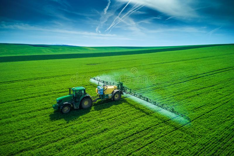 Aerial view of farming tractor plowing and spraying on field royalty free stock image