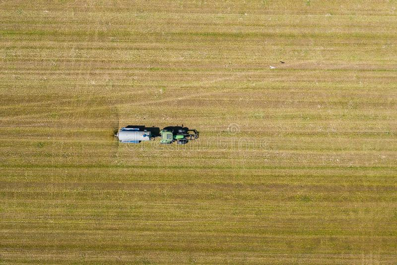 Aerial view of farming tractor plowing and spraying on field.  Agriculture. View from above. Photo captured with drone royalty free stock photo