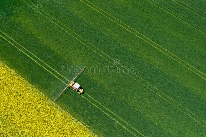 Aerial view of farming tractor plowing and spraying on field.  Agriculture. View from above. Photo captured with drone royalty free stock photography