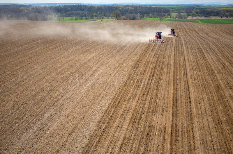 Aerial view of the field. Aerial view of the the tractor harrowing the large brown field in spring season stock images