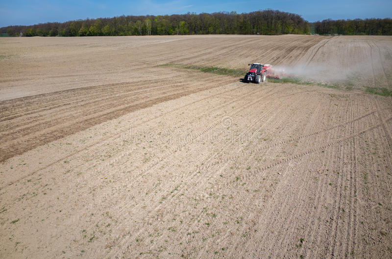 Aerial view of the field. Aerial view of the the tractor harrowing the large brown field in spring season stock photos