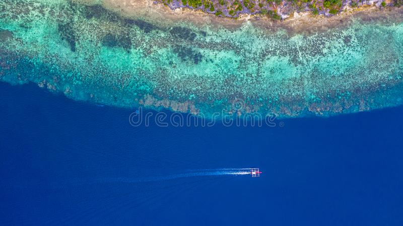 Aerial view of Filipino boats floating on top of clear blue waters, Moalboal is a deep clean blue ocean and has many local royalty free stock images