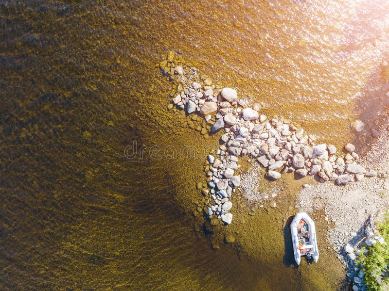 Aerial view of a fishing motor boat in the lake. Beautiful summer landscape with ships. Clear water with sandy and stone beach at. Sunset. Top view of yachts royalty free stock photo