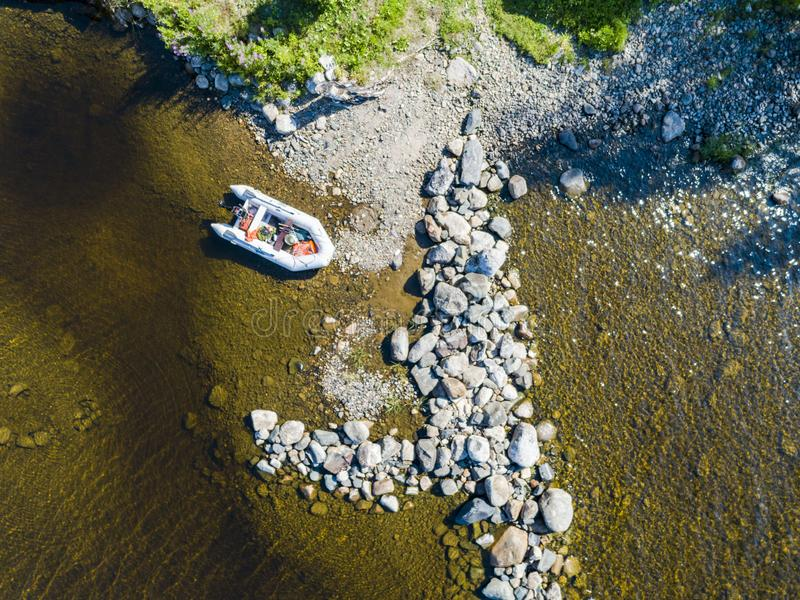 Aerial view of a fishing motor boat in the lake. Beautiful summer landscape with ships. Clear water with sandy and stone beach at. Sunset. Top view of yachts royalty free stock image