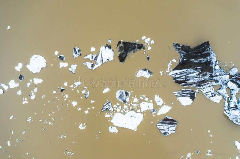 Aerial view of floating icebergs from glacier melt into the lake water as a result of global warming, seen from a drone above. royalty free stock photos