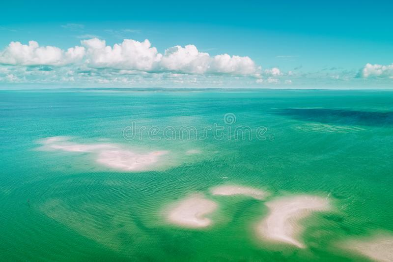 Aerial view of fluffy clouds over shallow ocean water. Aerial view of fluffy clouds over vivid turquoise shallow ocean water and patches of sand stock photography