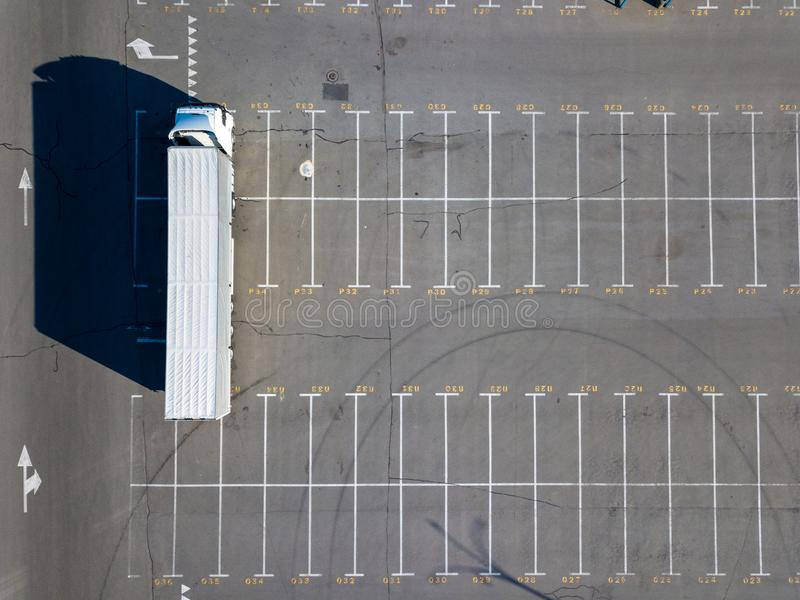 A long truck in a parking lot with markings for loading with building materials with sharp shadows on a sunny day royalty free stock photo