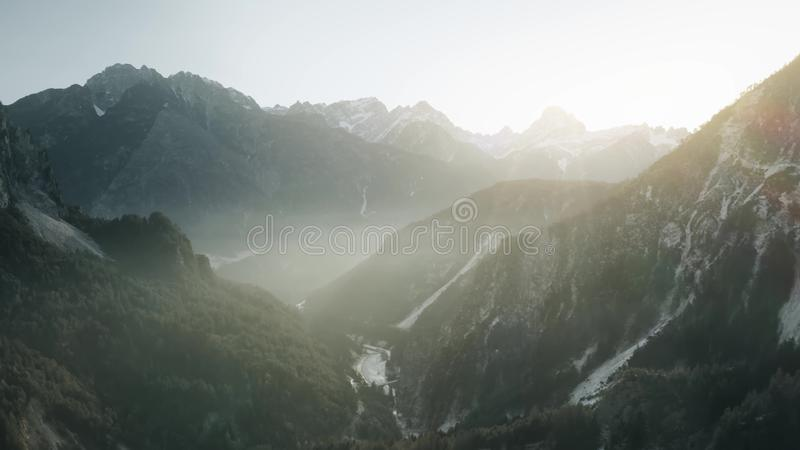 Aerial view of a foggy snowy valley in northern mountains, Italy royalty free stock image