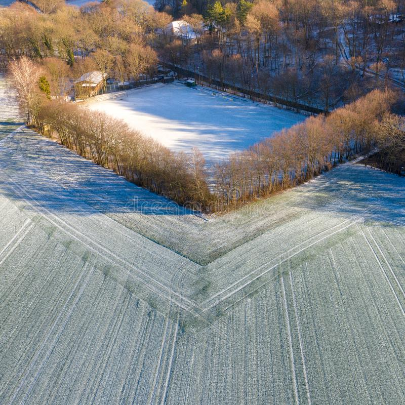 Aerial view of a football field of a district league team in a village with the first snow of the year. Drone shot royalty free stock photo