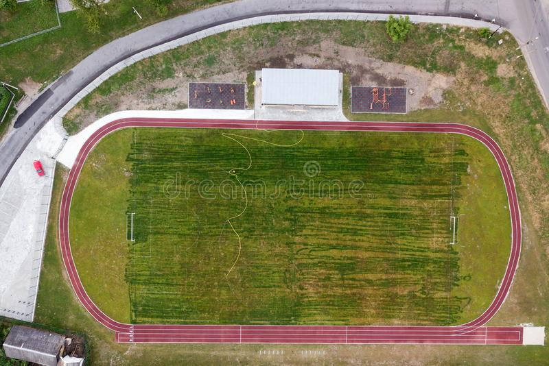 Aerial view of a football field on a stadium covered with green grass in rural town area.  stock images