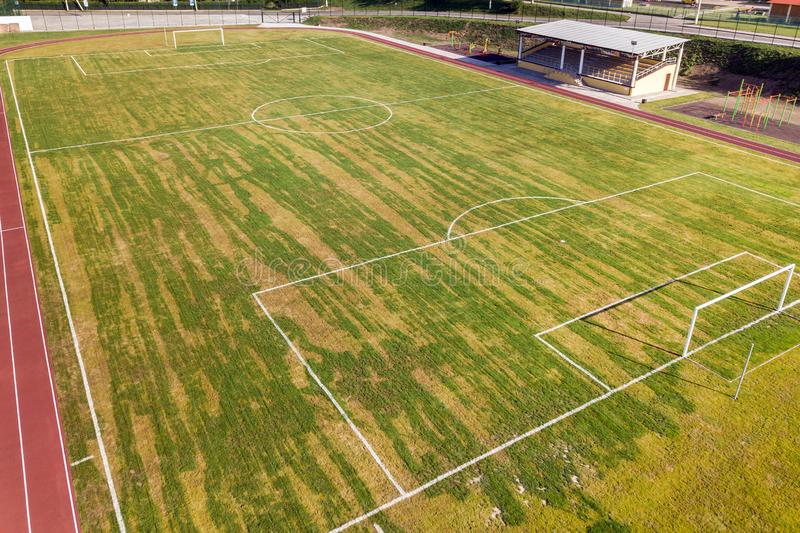 Aerial view of a football field on a stadium covered with green grass in rural town area.  royalty free stock image