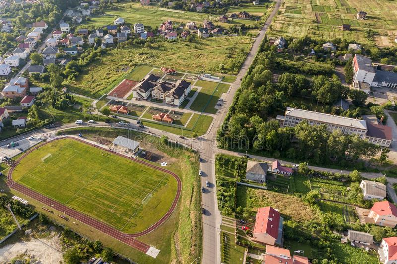 Aerial view of a football field on a stadium covered with green grass in rural town area.  royalty free stock photos