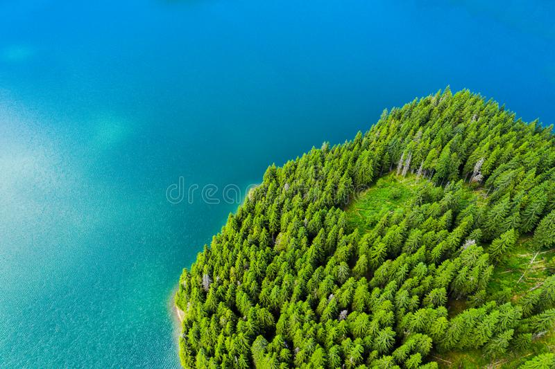 Aerial view of a forest lake. Aerial view of blue lake and green forests on a sunny summer day. Drone photography. Forest and lake stock photography