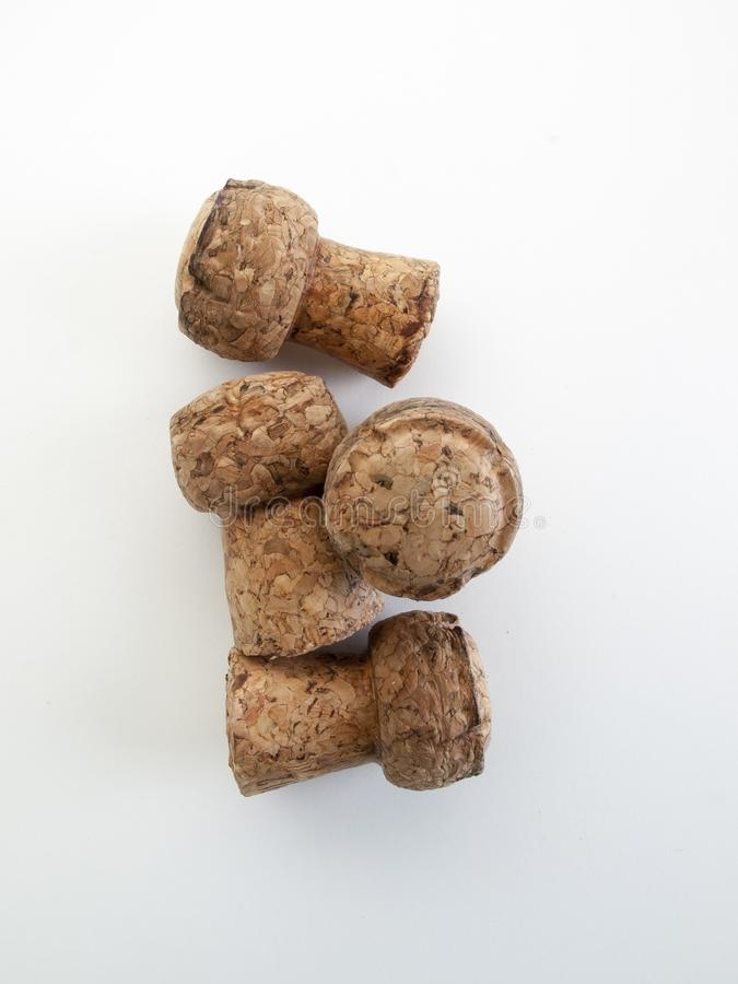 Aerial view of four champagne corks on a white table. Aerial view of four champagne corks piled on a white table and background stock image