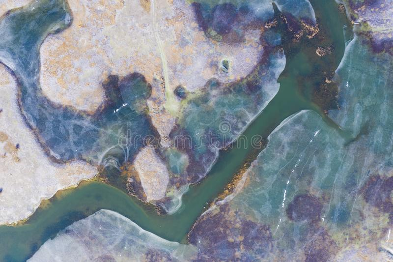 Aerial view of the frozen colourful lake melting because of the global warming. Famous intermittent lake in the winter stock photos