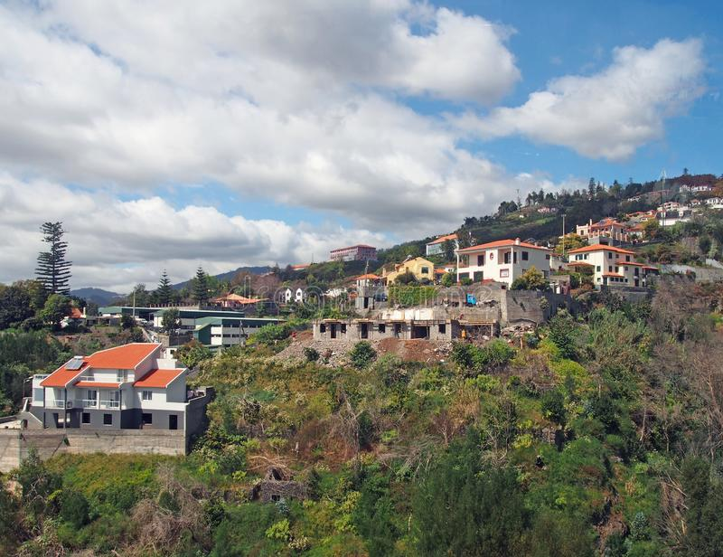 an aerial view of funchal in madeira with houses and farms on a mountainside with the city and coast in the distance stock image