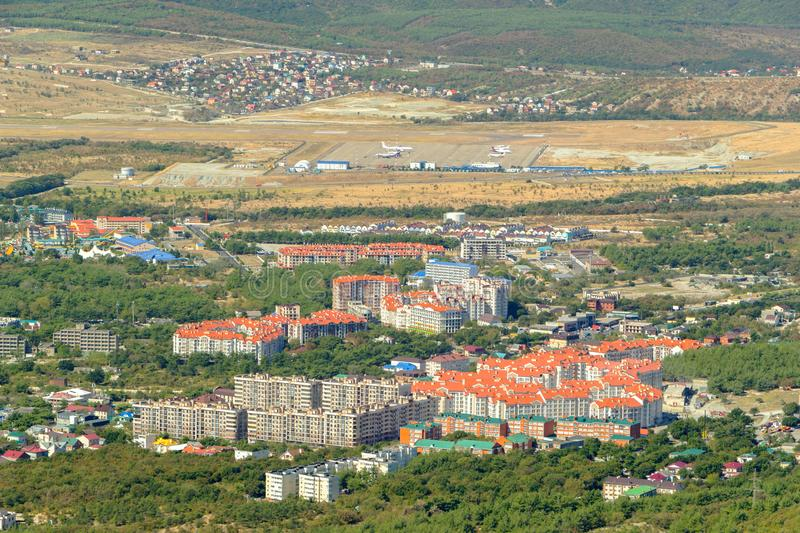Aerial view of Gelendzhik resort city district from hill of caucasian mountains. Airport runway strip and aquapark in. Aerial view of Gelendzhik resort city stock image