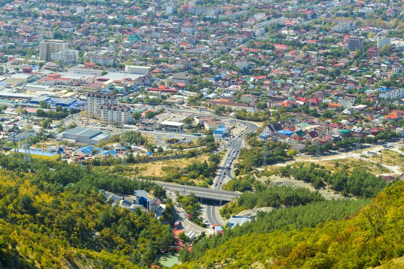 Aerial view of Gelendzhik resort city district from hill of caucasian mountains. Buildings and street at the foot of the. Mountains. Daylight sunrise photo in royalty free stock photos