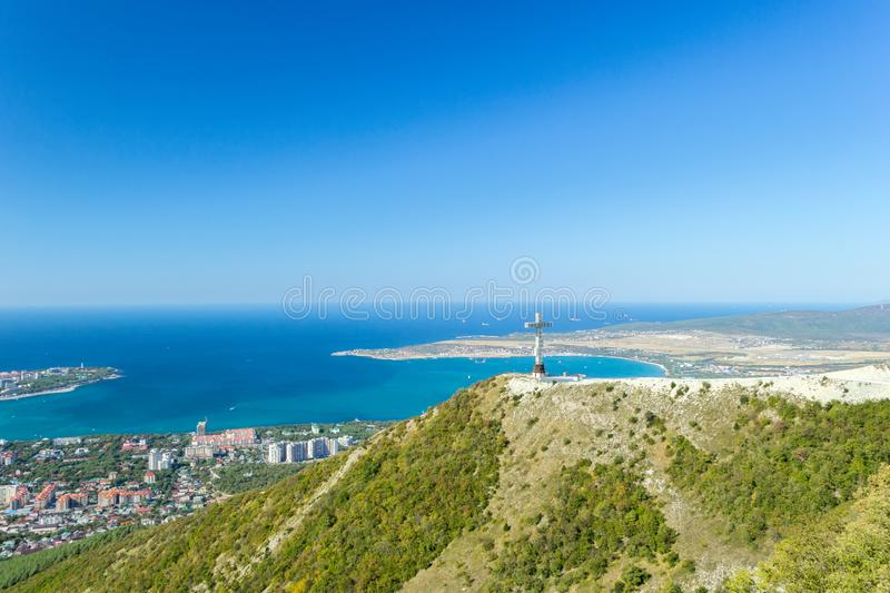 Aerial view of Gelendzhik resort city from hill of caucasian mountains. Worship cross monument on hill. Aerial view of Gelendzhik resort city from hill of royalty free stock photos