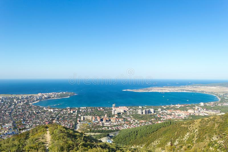 Aerial view of Gelendzhik sea bay. Photo of resort city from hill of caucasian mountains. Buildings, beaches, ships and boats in blue water of sea bay and stock image