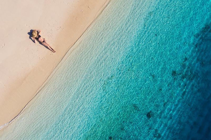 Aerial view of a girl on the beach on Bali, Indonesia. Vacation and adventure. Beach and turquoise water. Top view from drone at b. Each, azure sea and relax royalty free stock photography