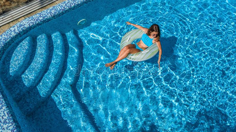Aerial view of girl in swimming pool from above, kid swim on inflatable ring donut, fun in water on family vacation. Aerial view of girl in swimming pool from royalty free stock images