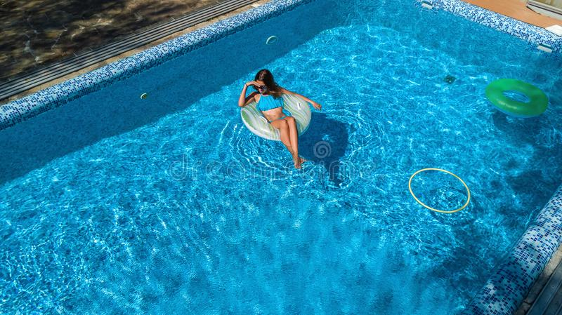 Aerial view of girl in swimming pool from above, kid swim on inflatable ring donut, fun in water on family vacation. Aerial view of girl in swimming pool from royalty free stock photo