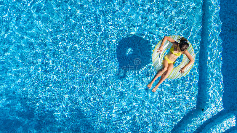 Aerial view of girl in swimming pool from above, kid swim on inflatable ring donut in water on family vacation royalty free stock image