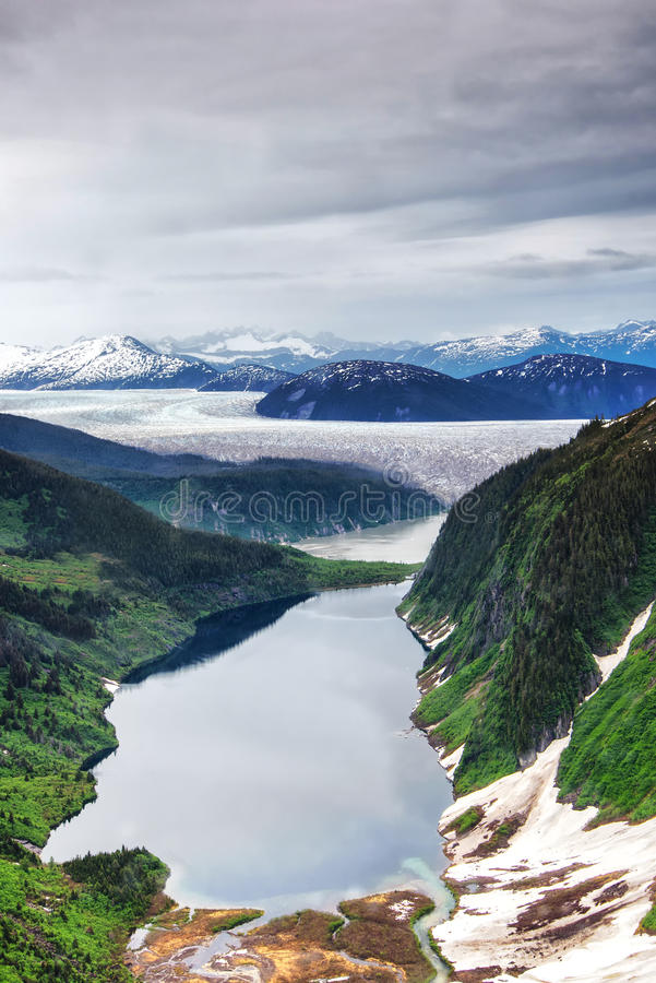 Aerial view of glacier in Alaska. Aerial view of Alaska snow capped mountains and melting glacier, lakes and ponds stock images