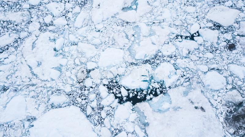 Aerial view of glacier broken into icebergs. Aerial view of fracktured glacier broken into icebergs floating on the sea. Disko bay, Greenland royalty free stock images