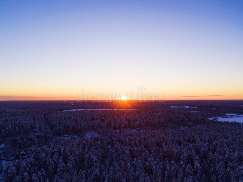 Aerial View Of A Gold Sunset Over Winter Snow Covered Pine