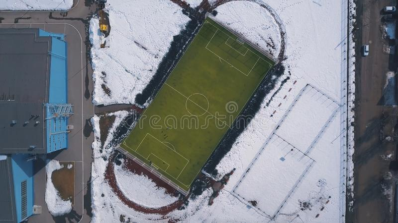 Aerial view of green football field and people playing football in winter. Clip. Hard trainings in winter season. Aerial view of green football field and people royalty free stock photo