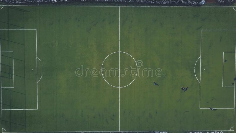 Aerial view of green football field and people playing football in winter. Clip. Hard trainings in winter season. Aerial view of green football field and people stock photo