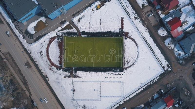 Aerial view of green football field and people playing football in winter. Clip. Hard trainings in winter season. Aerial view of green football field and people stock photos