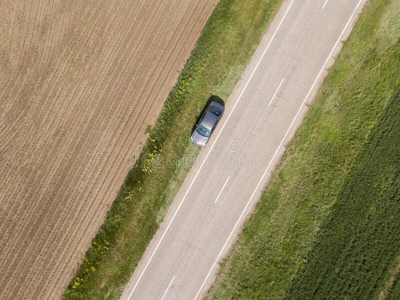 Aerial view of green summer field with a road. Captured from above with a drone royalty free stock photography