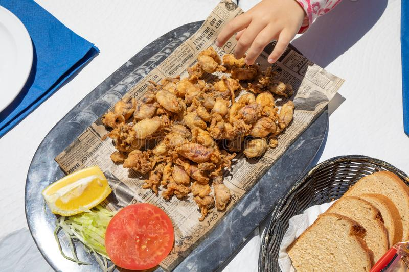 Aerial view of hand of child taking fried baby squids on tray stock image