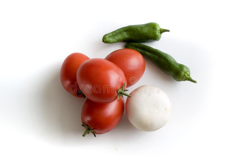 Aerial view of a handful of pear tomatoes, an onion and two green peppers royalty free stock photography