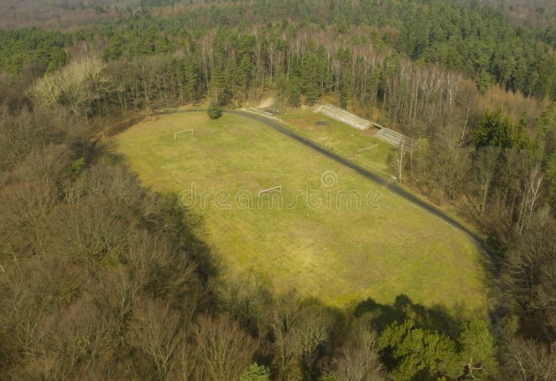 Aerial view on hidden football stadium in deep forest, including ruined fan stand, treadmill and gates. Aerial view on hidden football stadium in deep forest royalty free stock photos