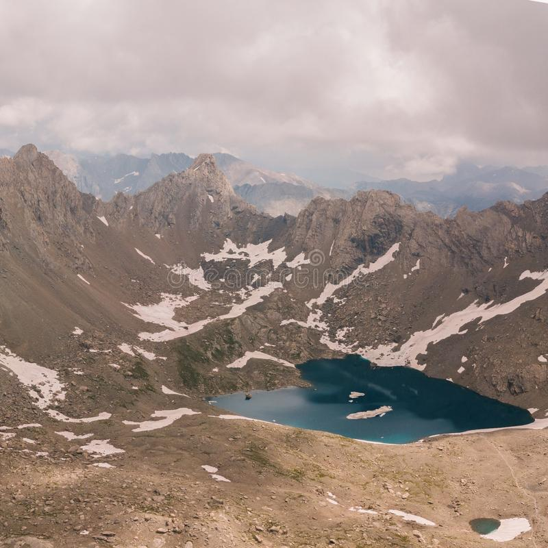 Aerial view of a High mountain lake surrounded by snow spots cloudy sky and sun spots on the rocks royalty free stock photography