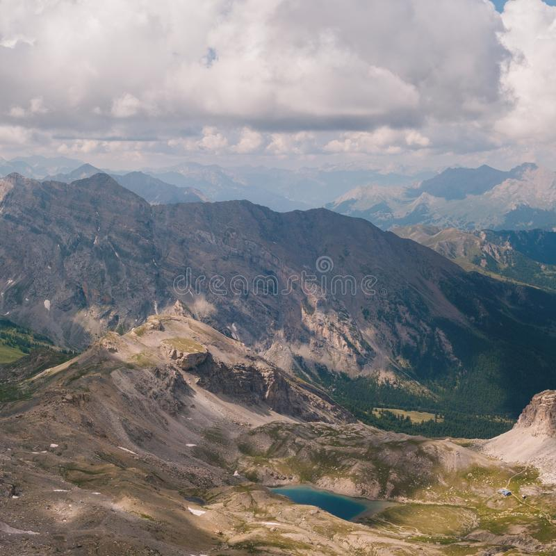 Aerial view of a High mountain valley with a small blue lake down the mountain clouds in the sky and sun spots on the cliffs stock photo