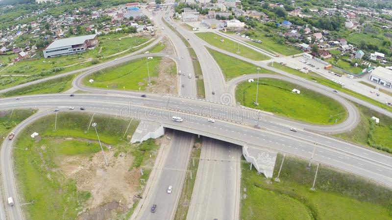 Aerial view of highway in city. Clip. Cars crossing interchange overpass. Highway interchange with traffic. Aerial bird royalty free stock photos