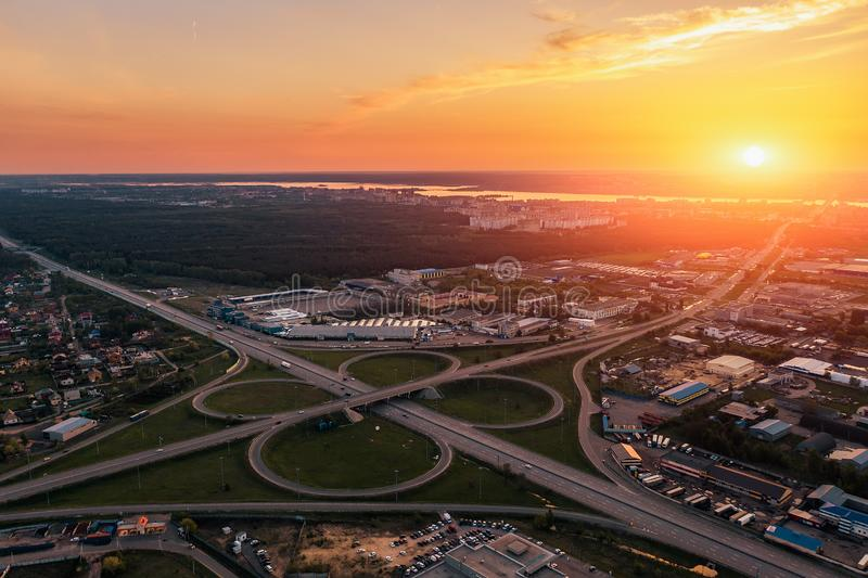 Aerial view at highway intersection or road junction with circle movement at sunset, cars and trucks traffic royalty free stock image