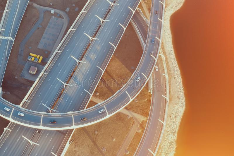 Aerial view highway loop over a road junction in the evening at sunset royalty free stock image