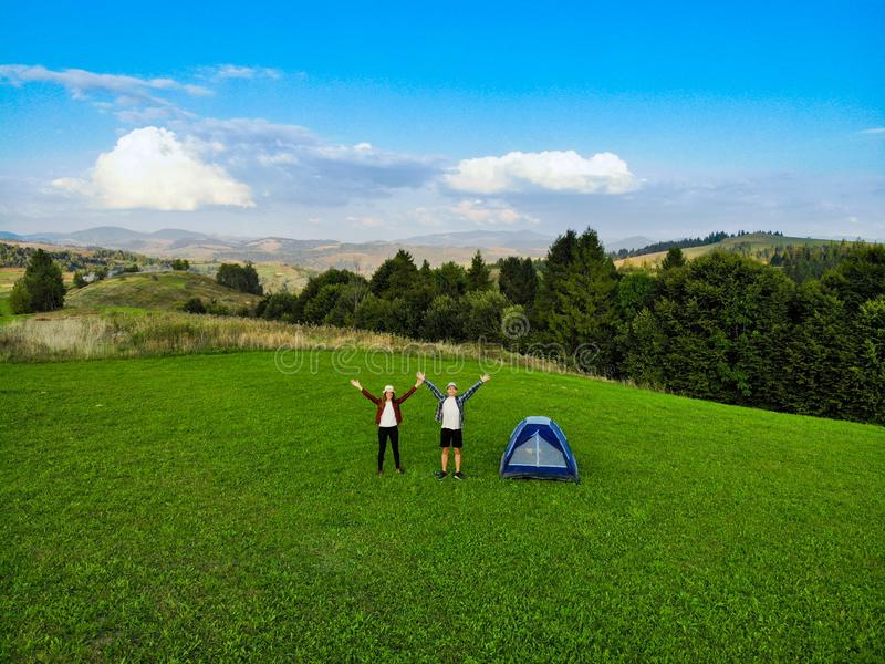 Aerial view of hiker couple raised hands up to sunlight on green grass in mountain near camping. stock photo